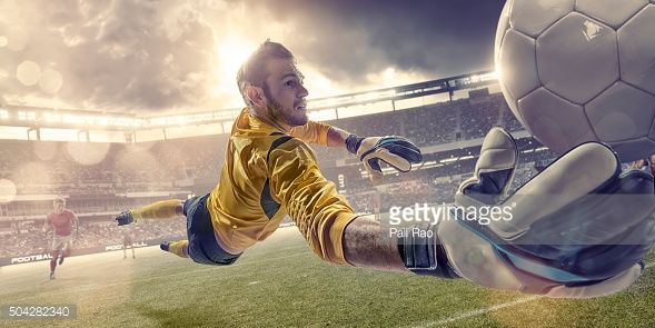 Stock Photo : Football Goalkeeper Diving To Save Ball During Soccer Match