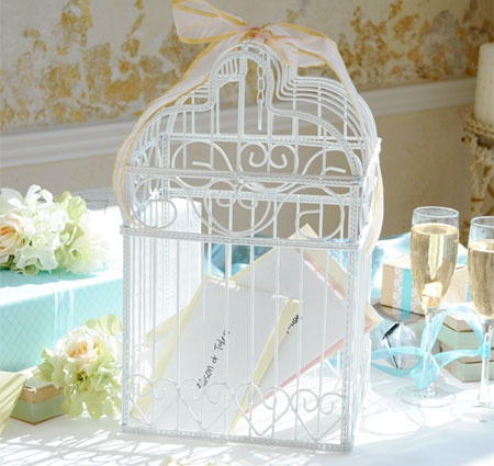 This white metal framed birdcage card holder is decorated with a scrolled heart motif making it a beautiful addition to a gift table to collect cards or wedding wishes from your guests.