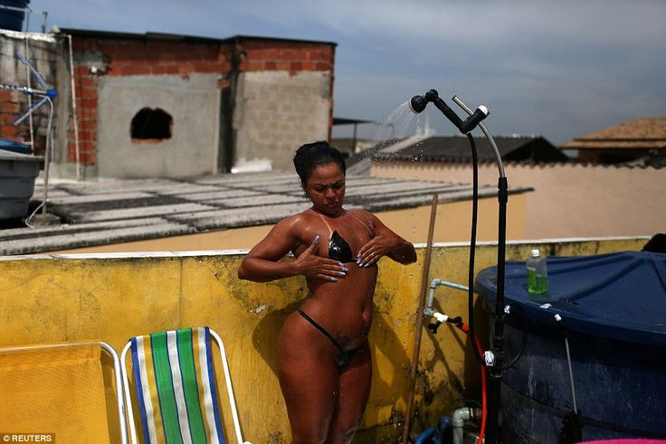 Time for a break: One woman takes a shower to refresh herself during sunbathing to have th...