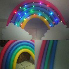 Arco-íris feito com Macarrão de Piscina e luzes de LED. Criei esse arco-íris lindo utilizando Macarrão destes de piscina. Prendi o primeiro com linha. Em seguida fui prendendo os seguintes com fita durex larga. Depois de prender os macarrões... Encaixei os pisca pisca O resultado ficou sensacional!