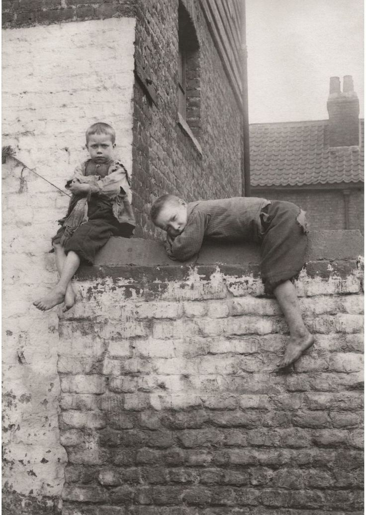 "The Spitalfields Nippers show the East End before the welfare state. This photo of boys sitting on a wall is captioned simply ""Brothers"""