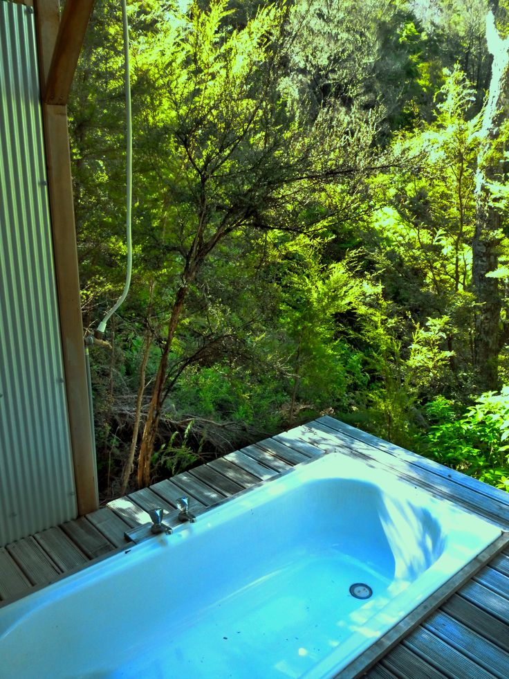 This beautiful outdoor bath overlooks dense bush. Tasman NZ