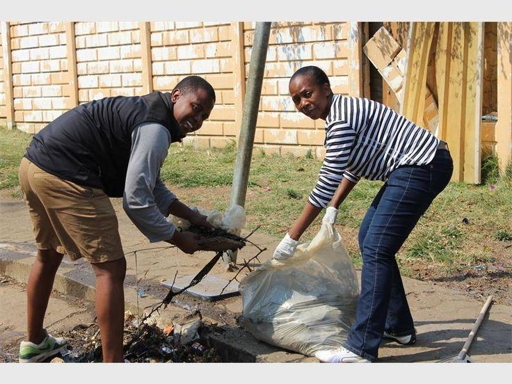 Moeti Moalosi and Stephy Moumakwe pick up rubbish on Beatrice Street.