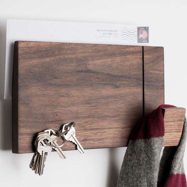 Organize your entryway in style with this multi-purpose wood wall rack. A great look in maple or walnut and a must-have for on-the-go households!    Modern design has a built-in mail slot in back for grab and go convenience   Made from solid maple or walnut   Multi-function front includes a scarf or coat hanger, magnetic key holder and serves as a tack board for important reminders  ...