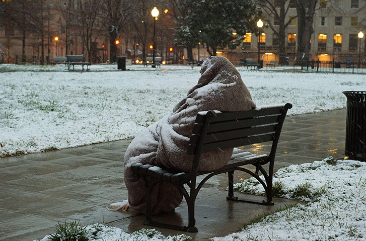 A homeless man sits covered in snow early in the morning in Washington DC