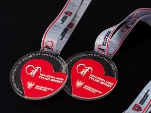 """Medale sportowe dla kampanii """"Uzależnia mnie tylko sport"""" Medale z przezroczystej pleksi i czerwonego laminatu."""