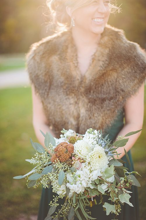 Pair forest green bridesmaid dresses with fur stoles for a fall wedding | Brides.com