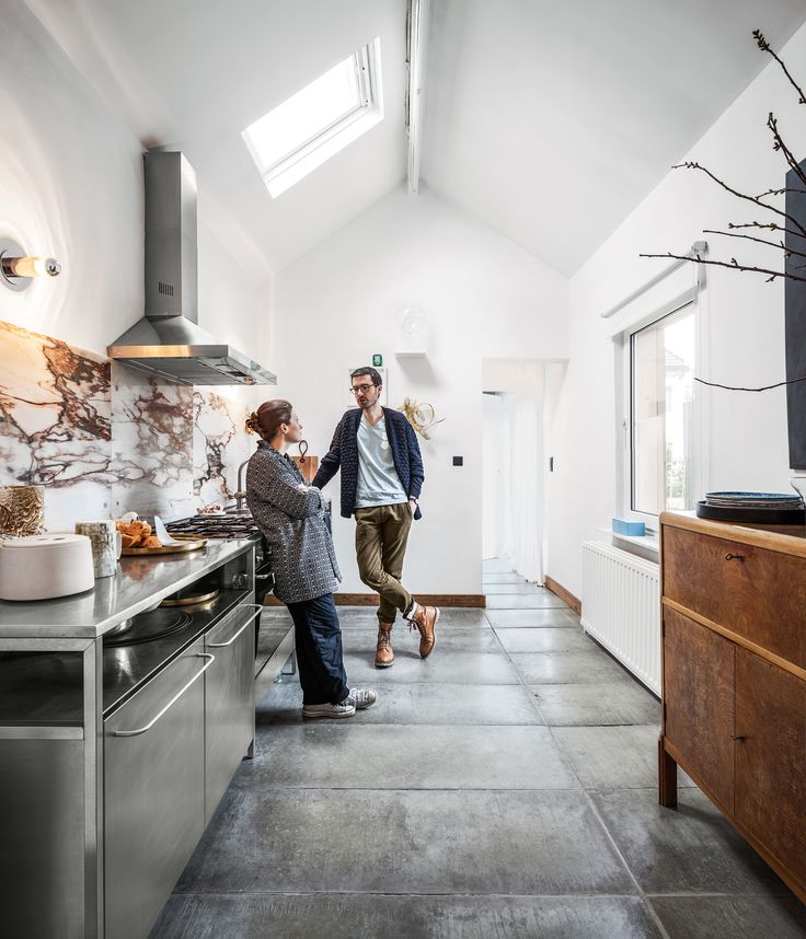 For the new kitchen, they incorporated a Smeg cooktop, oven, and range hood, stainless steel cabinets from Habitat, and personal accessories like a prototype goblet.