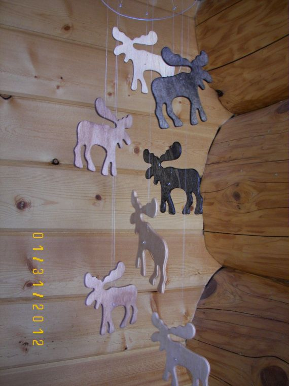 This mobile is made with 9 wooden moose that have been stains in 3 differents shades of brown. A varnish has been applied for a finish. The moose