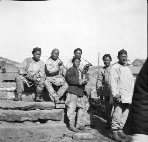 """California Historical Society Collection, 1860-1960 :: Title Insurance and Trust, and C.C. Pierce Photography Collection, 1860-1960 :: Photograph of """"Coolie"""" laborers smoking and resting on a rooftop in China, ca.1900. Six men are shown in pants and tunics, smoking from long pipes. """"Coolie"""" was the term used by a foreign shipping agency to denote a native laborer."""