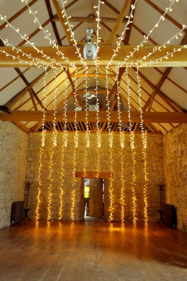 A gathered fairy light canopy at the barn at Notley Abbey for a late spring wedding