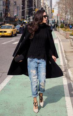 Street style look com blusa tricot preta, calça jeans e sobretudo.