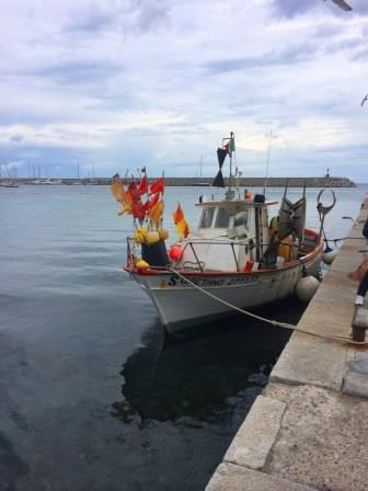 fisherman boat just arrived, selling its just caught fishes - marciana marina - Elba island - italy