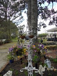 Repurposed Victorian Hall Tree for Hanging Flower Baskets.