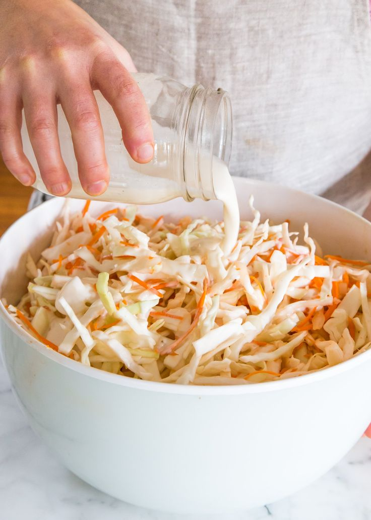 Making coleslaw and pouring the dressing