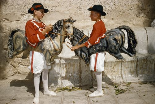Boys wear papier-mache horses to perform dance of Cavallets. Location: Felanitx, Mallorca Island, Balearic Islands, Spain.