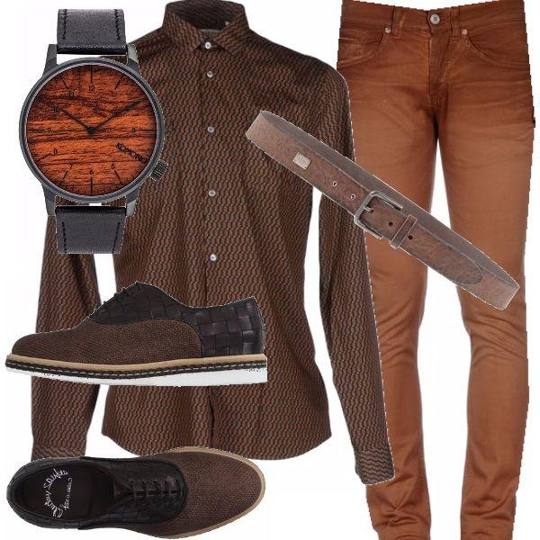 Tutto nella tonalità marrone l'outfit da uomo composto da un paio di pantaloni di taglio classico, la camicia con una delicata fantasia, le scarpe con dettagli a scacchi bicolore, la cintura e l'orologie con quadrante in legno.