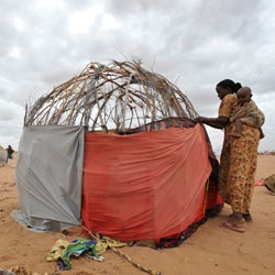 Isnino Siyat, 22, builds a flimsy, makeshift shelter with borrowed materials on her second night at Dadaab refugee camp in Kenya during last year's drought and food crisis in the Horn of Africa. (Jon Warren/World Vision): World Vision, Horns, Yurts, Buildings, Makeshift Shelters, Africans Building, Vision Blog