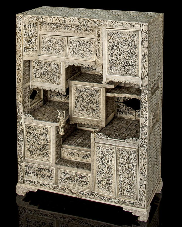 A pierced ivory cabinet with quail in grasses Meiji period (late 19th century) Of rectangular form with seven cabinet doors and three drawers carved in pierced and high relief with quail amongst foliage, framed with a formal border, the interior shelves engraved with diaper designs, the back open with silhouetted quail, the reverse and sides carved with simulated wickerwork, the interiors lacquered in gold nashiji