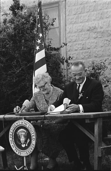 """President Johnson and his first school teacher Mrs. Kathryn Deadrich Loney—""""Miss Kate""""—sat together as President Johnson signed the Elementary and Secondary Education Act of 1965 into law  on Sunday, April 11, 1965."""