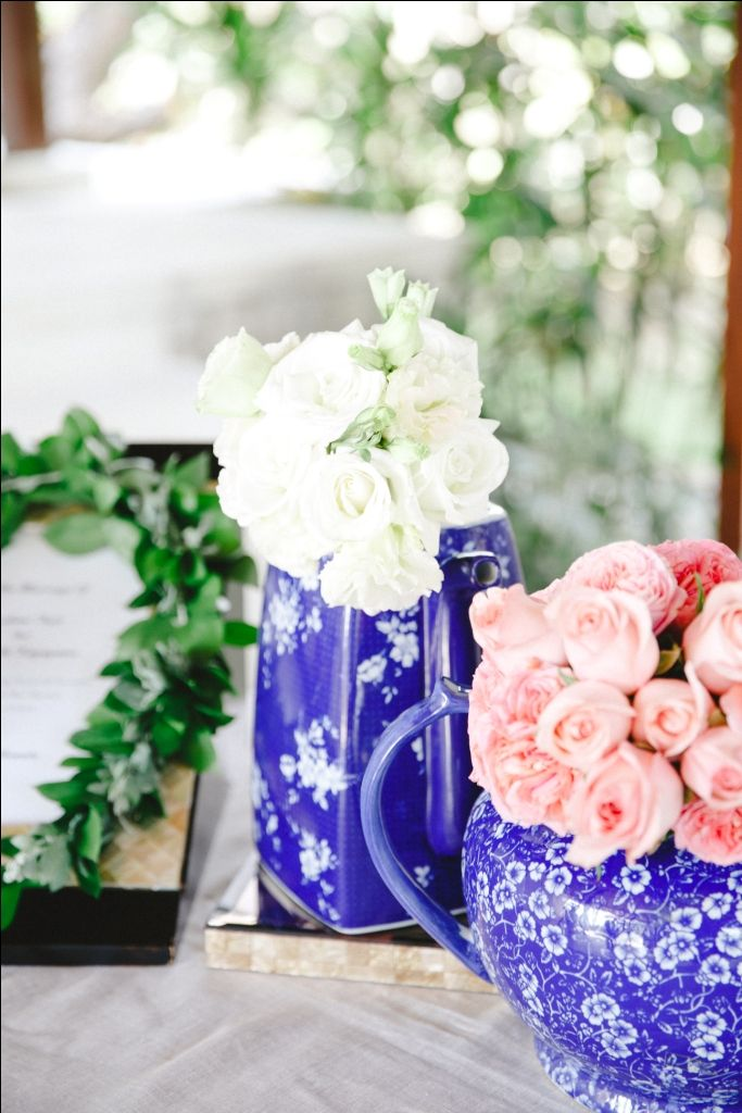Registration table adorned with white and pink flowers in blue jar