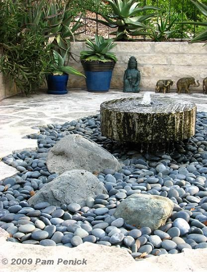 A free-form cutout filled with Mexican beach stones, a trio of small boulders, and a bubbling millstone fountain