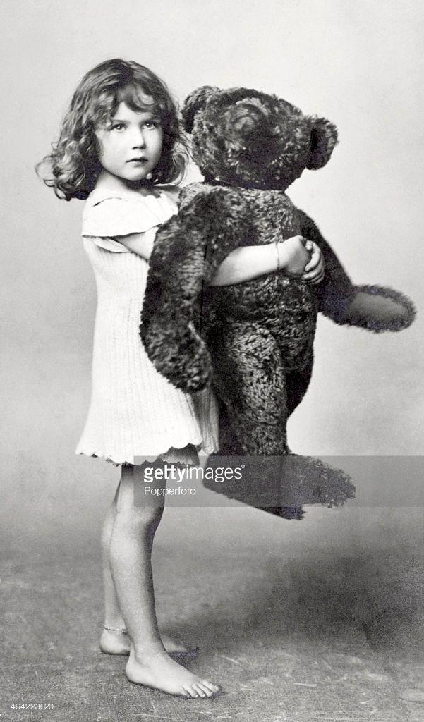 A vintage postcard featuring a little girl holding a large teddy bear, circa 1937.