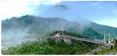 GRANDFATHER MOUNTAIN : Wonders Never Cease   Towering almost 6,000 feet above Northwest North Carolina, Grandfather Mountain presents guests with opportunities for rejuvenation, excitement and family memories in a natural haven that will endure for generations. Operated as a scenic travel attraction, Grandfather Mountain is a vast wild place, where knowledgeable guides and modern conveniences make a personal mountain adventure accessible to all.