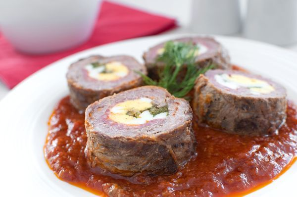 2 lb beef top round thinly sliced 1/2 lb sliced salami or prosciutto 3-4 hard-boiled eggs chopped 3/4 cup Parmigiano-Reggiano or Provolone cheese grated 1/2 cup flat-leaf parsley chopped 2 tbs garlic minced 1 tbs extra-virgin olive oil kosher salt & fresh ground pepper to taste tooth picks/butcher's twine Sauce 28 oz can crushed tomatoes w/ juices 1/2 cup dry red wine 1/4 cup tomato paste 1 bay leaf 1/2 tsp dried oregano 1/2 tsp dried basil kosher salt & fresh pepper to taste