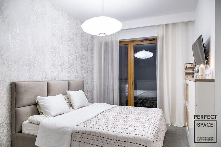 Przytulna i klimatyczna aranżacja sypialni z tapicerowanym, pikowanym zagłówkiem i połyskującą tapetą.