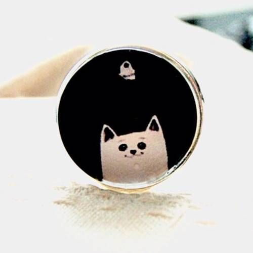 Bague cabochon chat blanc sur fond noir, en métal argenté.  - Un grand marché