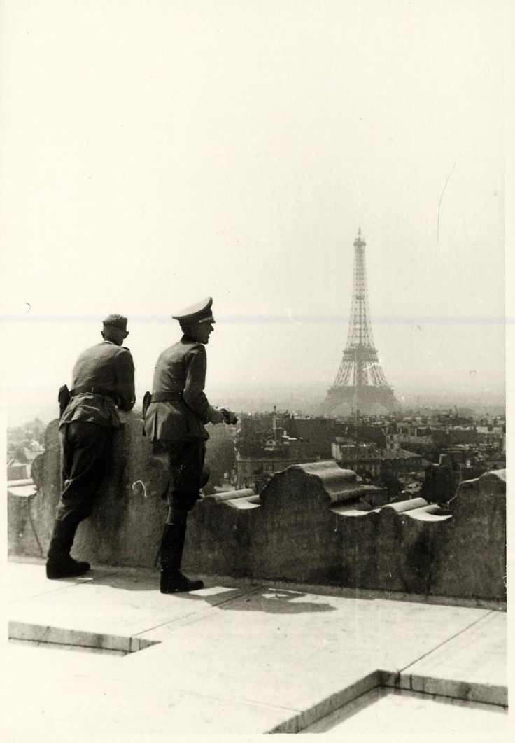 German Wehrmacht officers enjoy a brilliant view of the Eiffel Tower while stationed in the French capitol of Paris, not long after the country's swift capitulation to the German Reich. 1940.