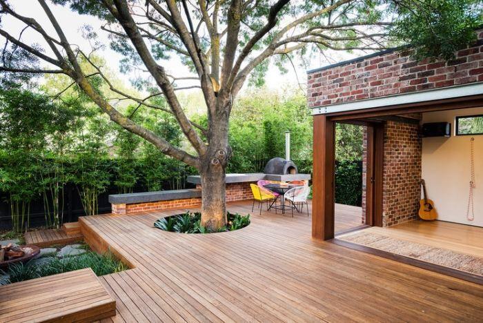 terrasse en bois avec un grand arbre, coin repas et cheminée