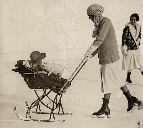 Pram on skis (sledge) on the ice, pushed by mom on skates. St. Moritz, Switzerland, 1926//