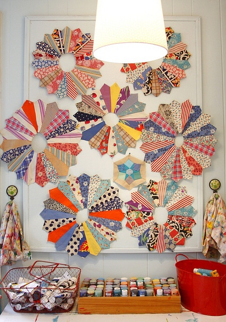 Casual, effective way to display the unfinished quilt squares you sometimes come across in antiques stores...