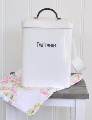 Få till en praktisk och snygg förvaring till ditt tvättmedel med denna plåtburk i vitt med svart text och skopa. Burken är delad i två delar inuti med text som märker upp vilken sida som är vittvättmedel och colurtvättmedel.