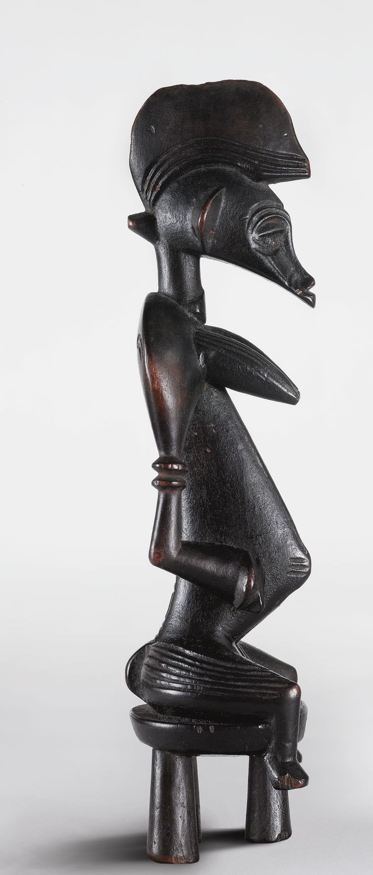 SENUFO SEATED FEMALE FIGURE, IVORY COAST - Small wooden antropomorphic statuettes were used by Senufo diviners, called Sando'o, to communicate with helpful spirits living in the wilderness. The name tugubele applies to both the spirits and the mediating statuettes. Artists creating tugubele followed closely the instructions given to them by the diviner who would have been told certain details about the figure's required appearance, gender, posture, scarification marks etc. directly by the…
