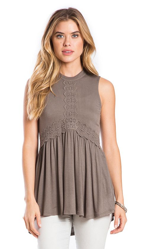 Be at one with nature in this soft knit babydoll tank with a high neck, trim on the center front and flowy waist area for ease and comfort. Model is wearing size Small.