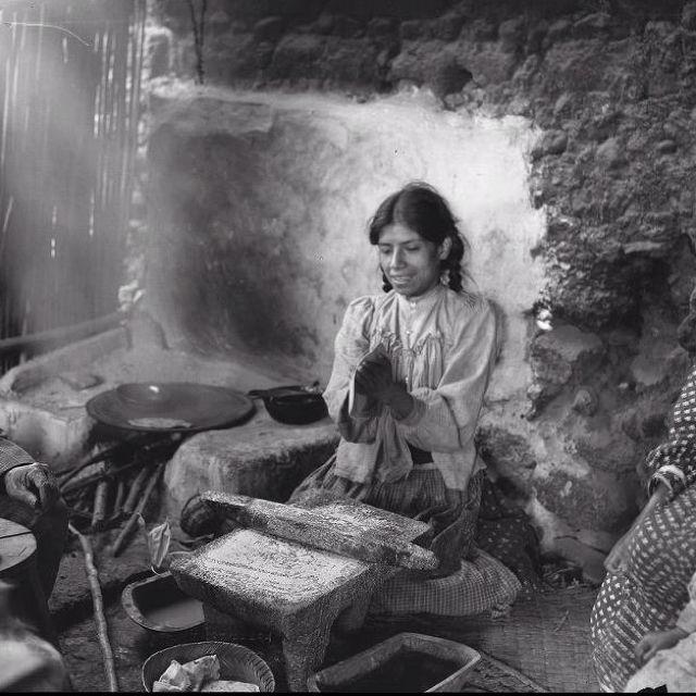 Una señora moliendo su maíz y haciendo tortillas.
