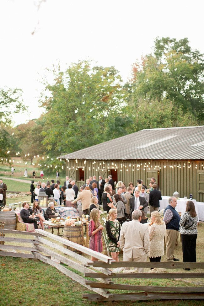 Love this outdoor receptions with hay bale seating and whiskey barrels as cocktail tables