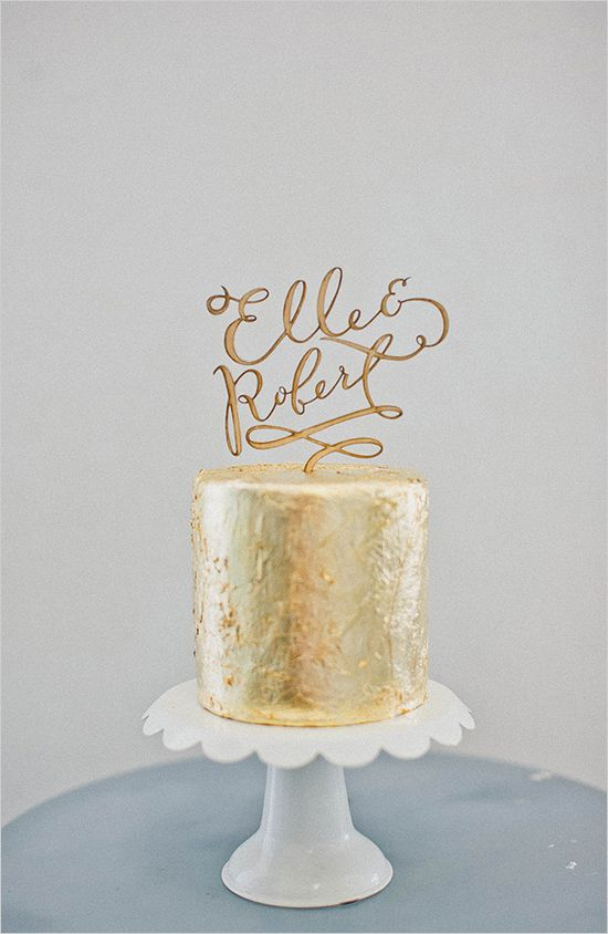 gold wedding cake with cool cake topper