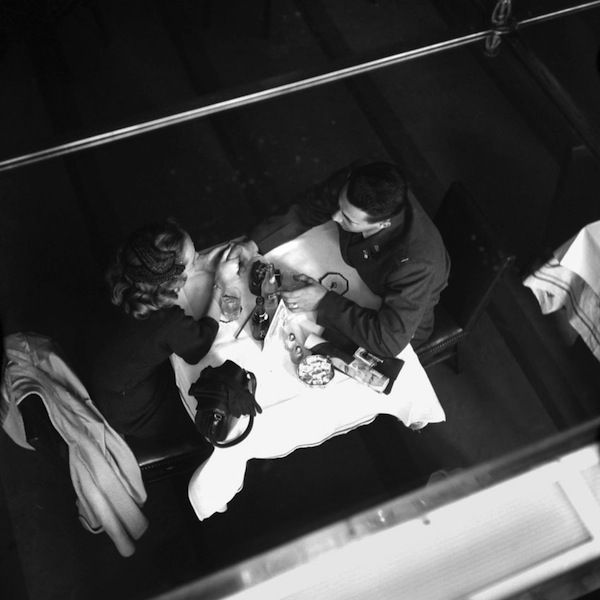 Vivian Maier.  / holding hands across the table
