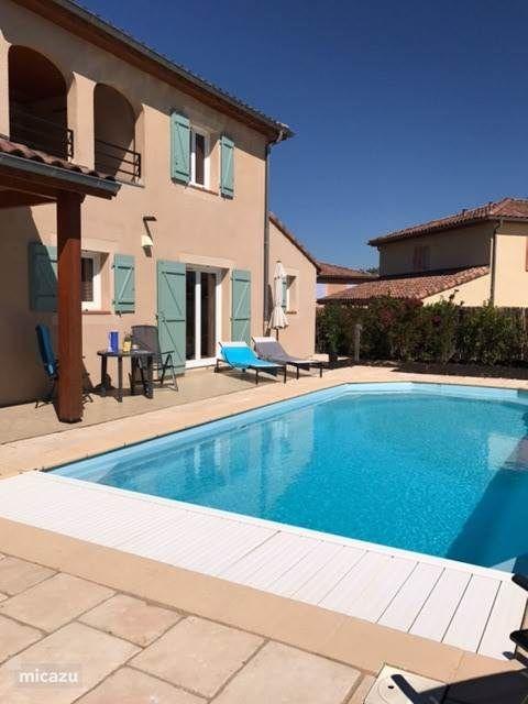 Een verwarmd zwembad met ligbedden en zitjes in zon en schaduw.