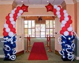 Patriotic balloon arch with blue, red and white latex balloons, white twisting balloons and two red mylar stars at the top.