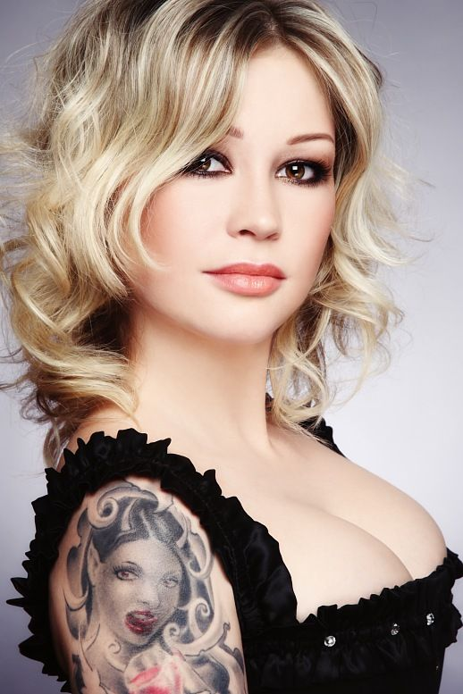 Russian blonde woman in corset with tattoo