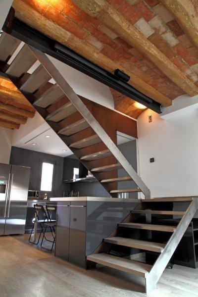 La escalera queda separada de la cocina gracias a una gran for Escalera de cocina