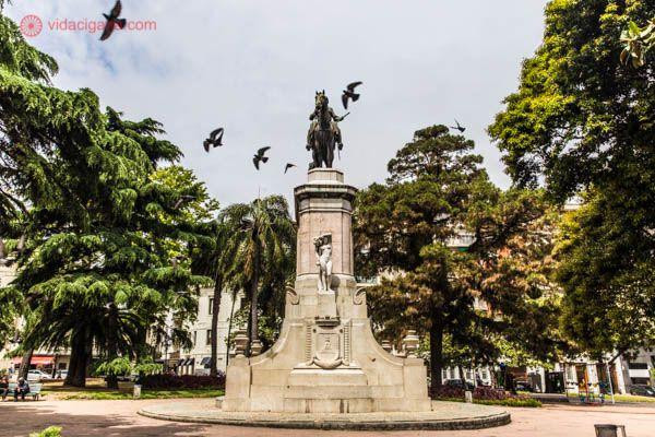 Plaza Zabala, em Montevidéu. Na foto, uma estátua equestre de Zabala se encontra no meio da praça. A estátua é cercada de árvores verdes e vários pássaros voando por cima da estátua. O céu está parcialmente nublado.
