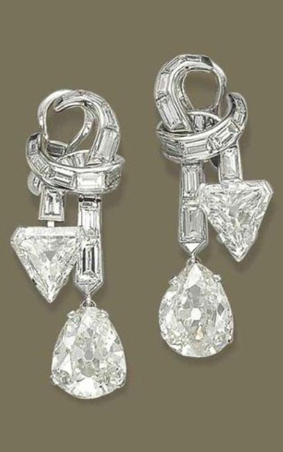 A PAIR OF VINTAGE DIAMOND EAR PENDANTS, 1950S. Each designed as a baguette-cut diamond ribbon bow, suspending a pear-shaped and triangular-cut diamond drop, mounted in gold, 4.6 cm