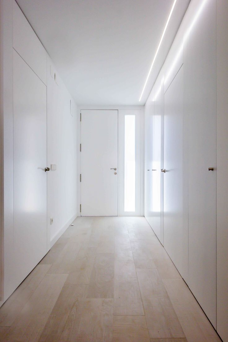 Recibidor con luz natural y armario con puertas enrasadas minimalista low cost en reforma de casa. Chiralt Arquitectos Valencia.