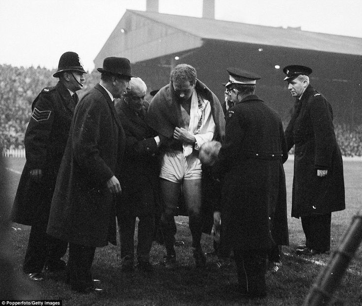 United's goalkeeper Harry Gregg is helped off the pitch after injuring his shoulder against Liverpool at Old Trafford in 1963 as Sir Matt Busby (second left) looks on anxiously